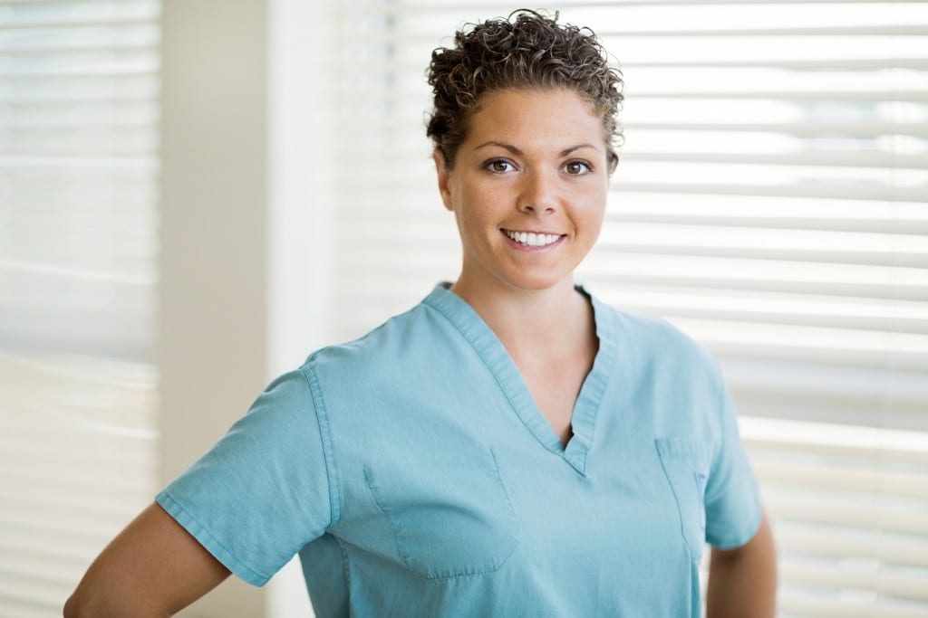 Portrait of happy female nurse in scrubs standing at clinic