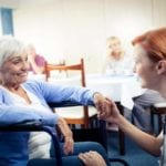 Nurse interacting with a senior woman in wheelchair in the retir